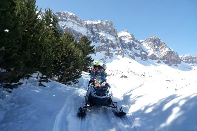 motos-de-nieve-accion-pirineos-pinos-y-pareja-en-moto