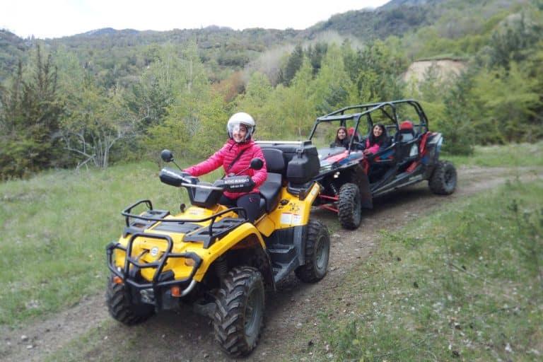 chicas-felices-vestidas-de-rojo-sonriendo-mientras-conducen-en-buggie-amarillo-y-quad-rojo