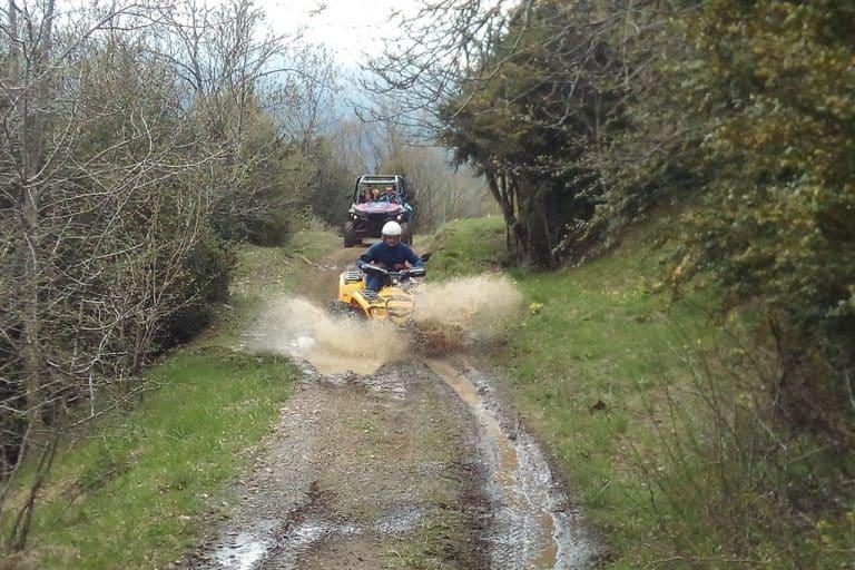 conductor-quad-amarillo-y-buggie-rojo-con-familiares-en-bosque-valle-de-tena-dia-lluvioso